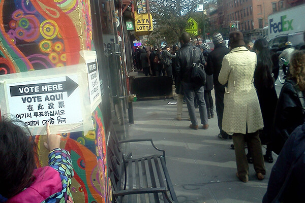 A line of people waiting to vote outside on a city sidewalk, a child points to a Vote Here sign taped to a colorful wall painted with a mural.