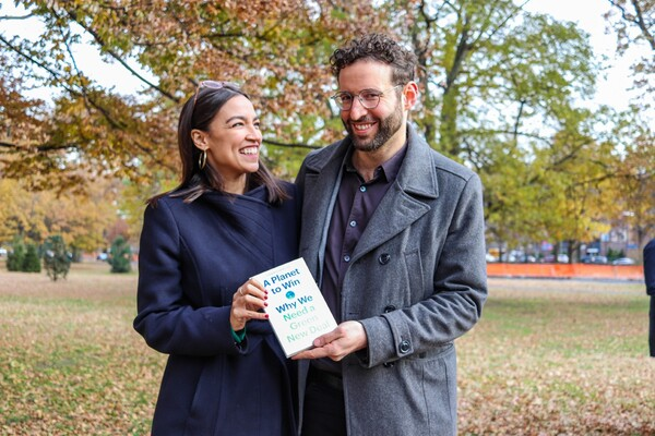 "Two people standing outside on a lawn covered in leaves, holding a book titled ""A Planet to Win, Why we need a Green New Deal."""