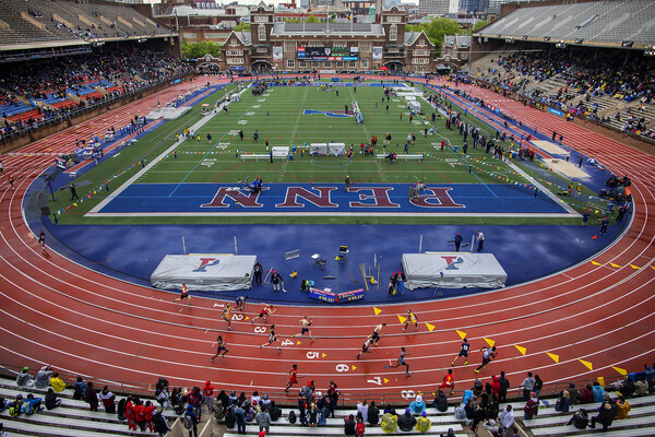 Runners race around the track at Franklin Field at the 2019 Penn Relays.