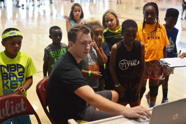 a person looking at a laptop surrounded by kids watching the screen standing in a basketball court