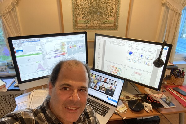 David Roos taking a selfie while teaching a class online, with scientific materials on the screen behind him