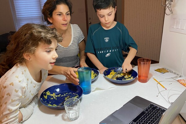A professor and two children eating from bowls at a kitchen counter with a laptop computer open in front of them.