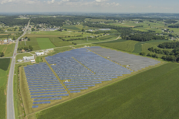 Aerial view of large greens landscape with solar panels set out over a large field.