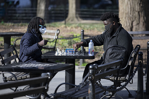 Two people sit in a public park in a city playing chess at a park table wearing protective face masks.