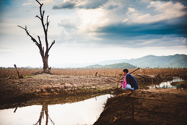 farmer sits on cracked earth near drying water source