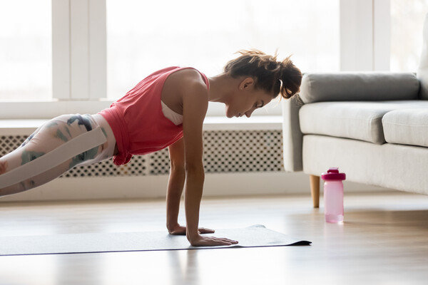 A woman does push-ups on a yoga mat in her living room near a couch and water bottle.