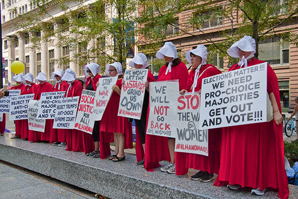 Line of protesters dressed as characters from The Handmaid's Tale holding protest signs