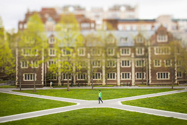 One person walking along the walkway at the Penn Quadrangle outside during the daytime