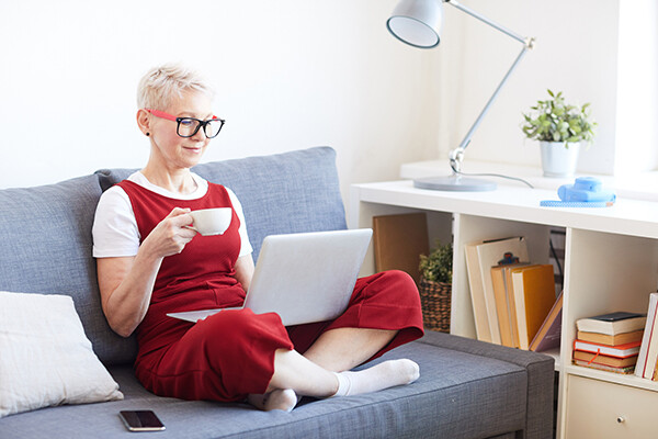 Person sitting cross-legged on a couch holding a tea cup looking at a laptop