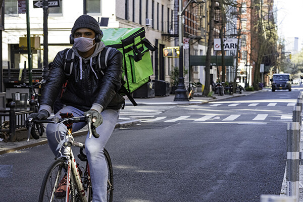 Bike food delivery courier wearing a protective face mask while riding through NYC empty streets