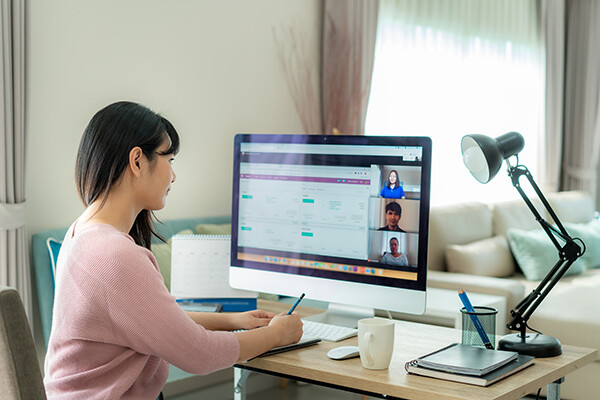 a person sits at a desktop computer at home watching a work video conference