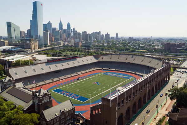 Penn's historic Franklin Field sits empty on a sunny day, with the Philadelphia skyline in the background.