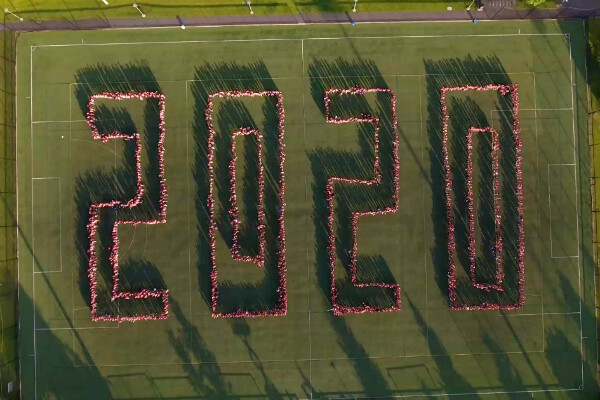 Bird's eye view of Penn Park with member of the class of 2020 standing on bright green grass and spelling out the number 2020 in an outline font.