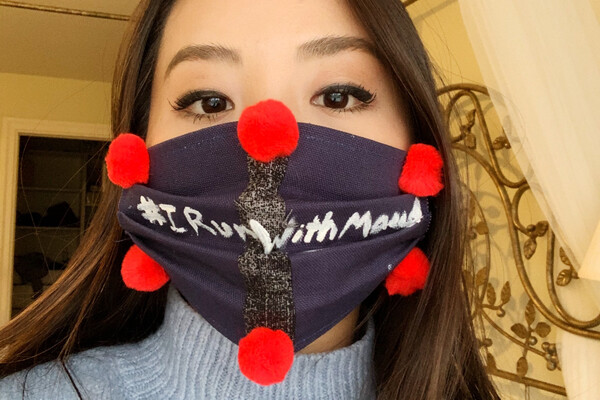 student wearing a dark mask with pom-poms with words #IRunWithMaud