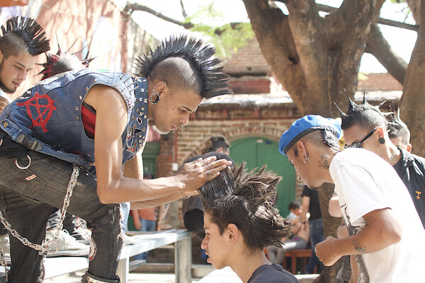 A young mohawked man with a leather vest featuring a red anarchy symbol styles another young man's hair into a mohawk