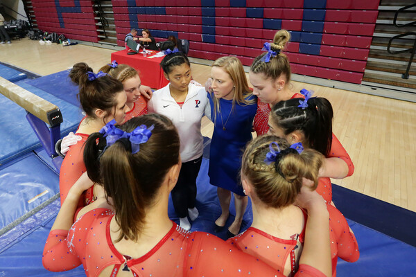 At a meet, Kirsten Becker and members of the gymnastics team huddle up.