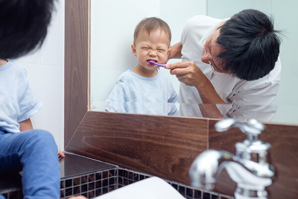 Parent brushes their toddler's teeth seen in a bathroom mirror