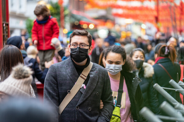 Not practicing social distancing, people walk down the street in close quarters wearing masks.