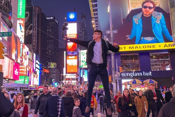 Young man holding a camera jumps above a trash can in the middle of busy Times Square