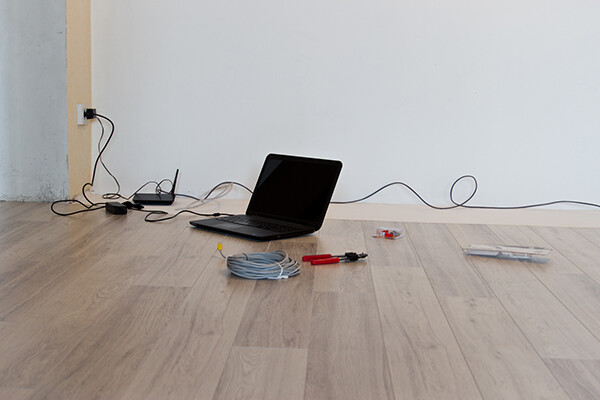 laptop on the floor of an empty room with cable, pliers and other tools for hooking up internet router and modem.