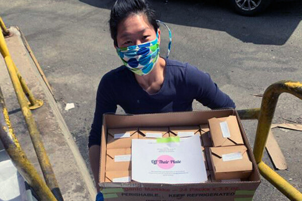 One of the founders of Off Their Plate wearing a face mask holding a box full of meals