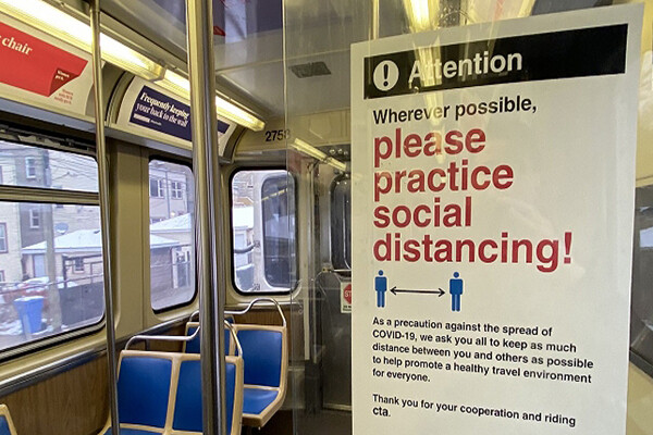 Sign on the wall inside an empty public transit trolley that reads Please practice social distancing.