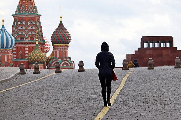 Person in black hooded jacket and pants facing away from camera walks near Red Square in Moscow.