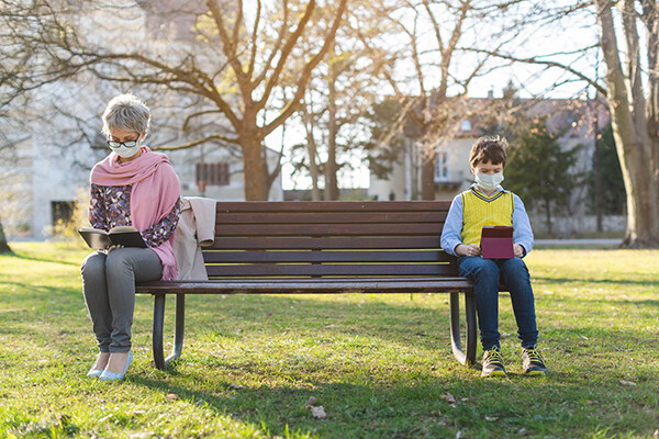 A grandparent and a child sit on a park bench in daylight, both wearing masks and sitting six feet apart.