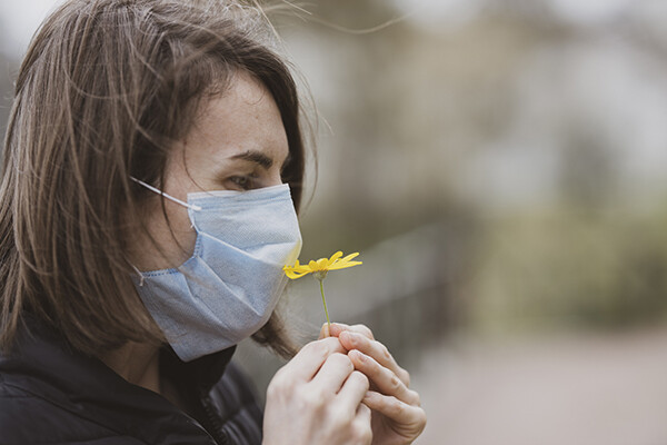 Person wearing a protective face covering holds a flower to their nose in attempt to smell its scent.