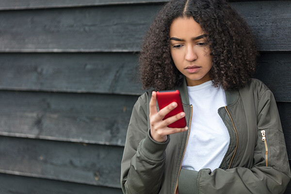 A teenager looks critically at a smartphone in their hand