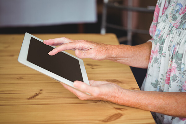 An elderly person's hands holding a iPad.