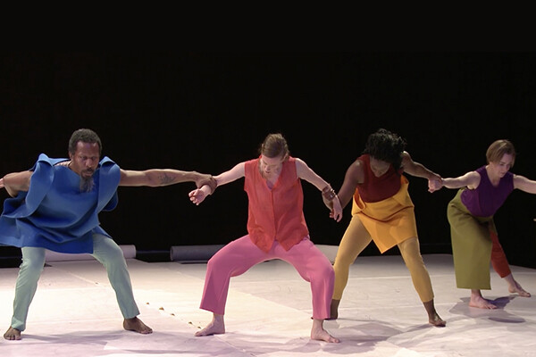 Members of a dance troupe linking arms in a line during a performance