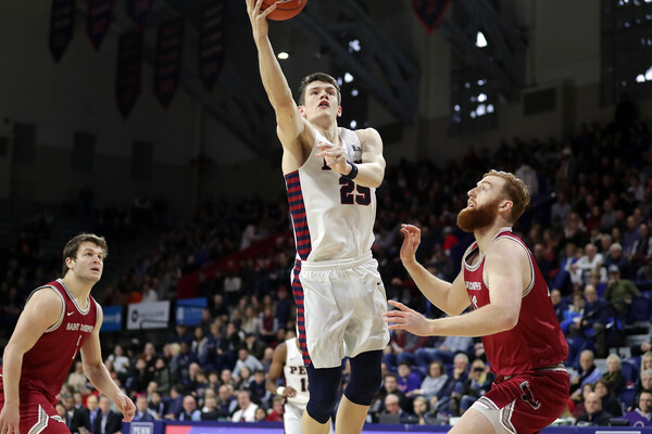 Forward AJ Brodeur of the men's basketball team lays the ball in the basket between two defenders at the Palestra.