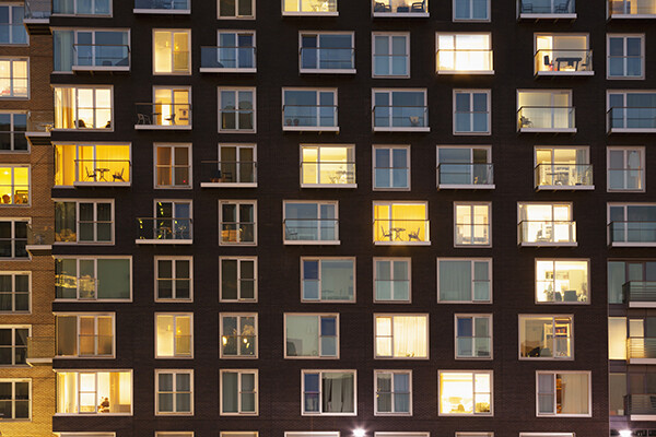 facade of apartment building at dusk with windows lit up
