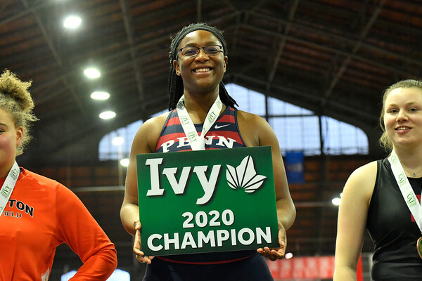 Mayyi Mahama holds a first place board while standing on the first place podium at the Ivy Heps.