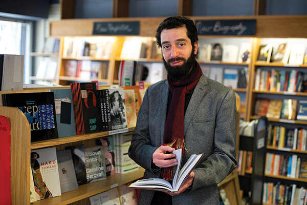 Ahmad Almallah stands in a bookstore holding a book.