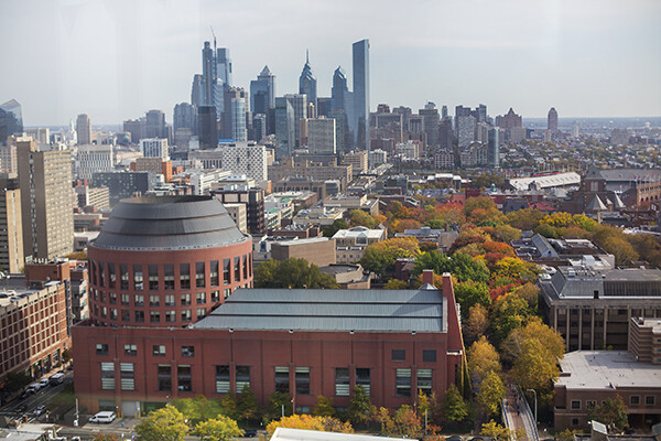 Aerial view of Wharton building on Penn campus with skyline of the city behind it