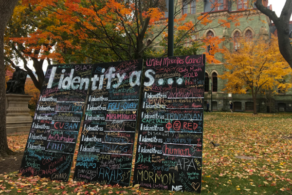 "Three blackboards in front of Claudia Cohen Hall say ""I identify as..."" with various descriptors written in colorful chalk (mormon, human, FGLI, queer, etc)"