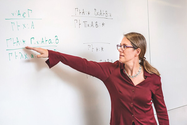 Stephanie Weirich stands pointing to a mathematical equation at a whiteboard.
