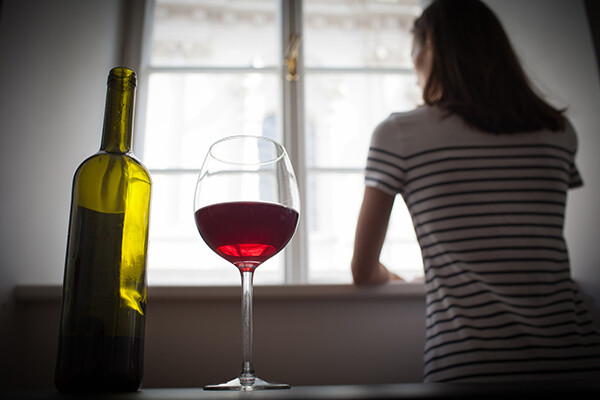 Person looks out of window with bottle and a glass of wine on a table