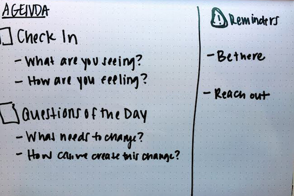 Writing on a whiteboard reading: Check-in, what are you seeing? What are you feeling? Question of the day: What needs to change? How can we create this change? Reminders: Be there. Reach out.
