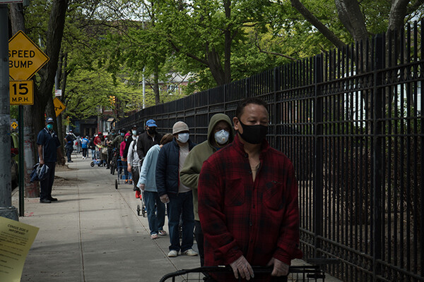 A line of people outside a food bank wait on a sidewalk practicing social distancing and wearing face masks.