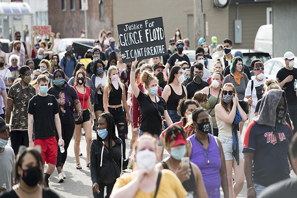 "A crowd of people wearing masks march in the streets, one protester holds a sign reading ""Justice for George Floyd."""