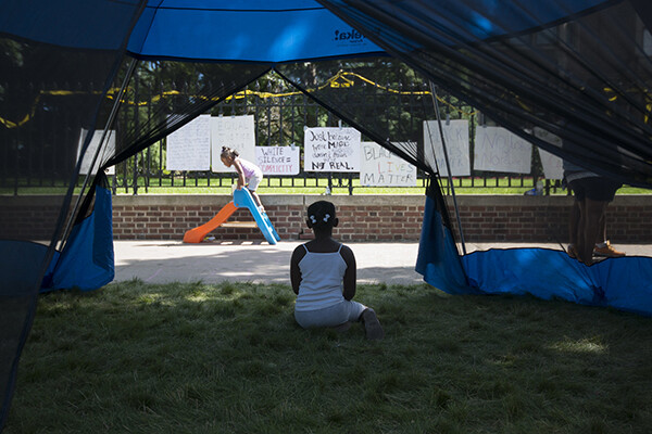 A child sits on the grass in front of a large fence covered in Black Lives Matter protest signs, another child plays on a small toy slide on the sidewalk in front of the fence.