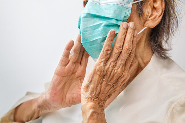 Elderly person holds their hands to their face wearing a medical face mask.