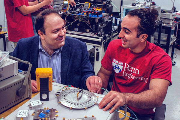 Firooz Aflatouni and a member of his lab sit at a table in his lab surrounded by engineering equipment.