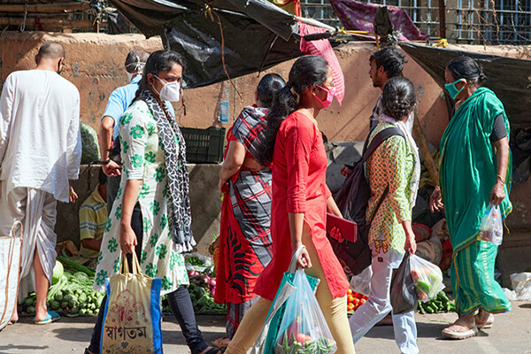 Several people wearing face masks walk through an outdoor market carrying bags of groceries in India