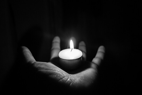 Open palm holding a small candle