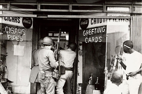 Historic image of police storming a storefront in 1967 during a riot in Detroit.