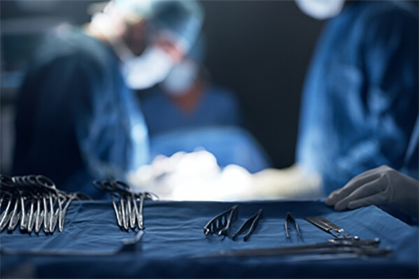 Closeup view of surgical tools on a tray while surgeons perform surgery in the background